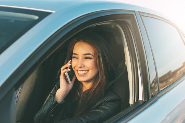 美しいブルネットの長い髪の若いアジア女性運転と携帯電話で話す