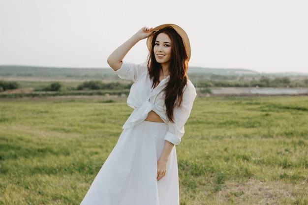 白い服と麦わら帽子で魅力的な屈託のない長い髪のアジアの女の子の肖像画は日没でフィールドでの生活を楽しんでいます