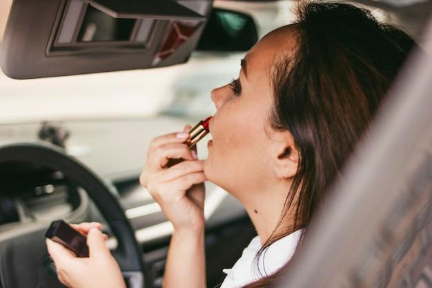 車の中で赤い口紅で唇を塗る美しい成功したエレガントなブルネット若い女性