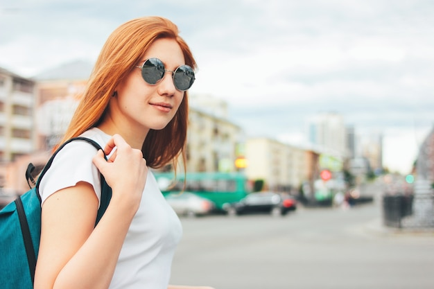 路上でバックパックとカジュアルな服装でサングラスで魅力的な赤毛笑顔の女の子