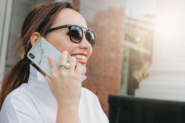 携帯電話を使用してサングラスでエレガントな女性ビジネスブルネットの肖像画を間近します。
