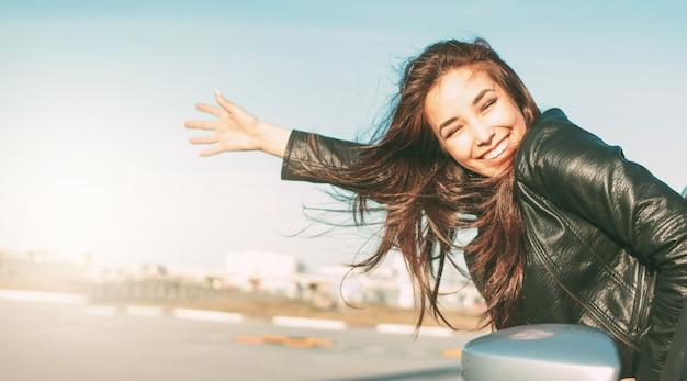車の中で黒い革のジャケットで幸せな美しい魅力的なブルネットの長い髪の若いアジア女性