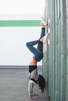 彼女の腕の上に立って若いブルネットの女性ストリートダンサー体操