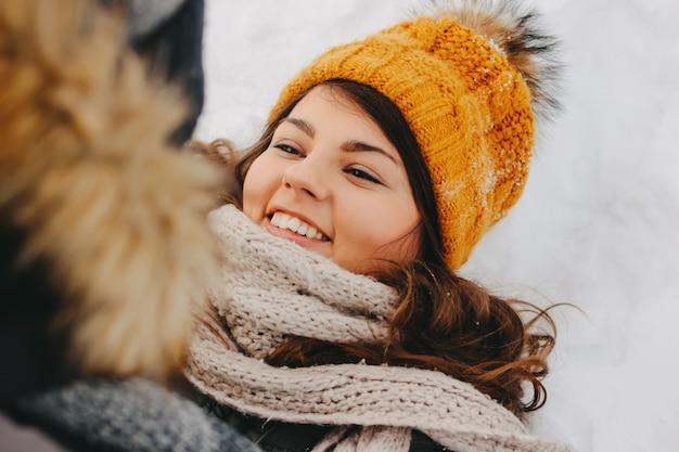 寒い季節の森林自然公園で幸せなカップル。黄色い帽子で幸せなブルネットの少女