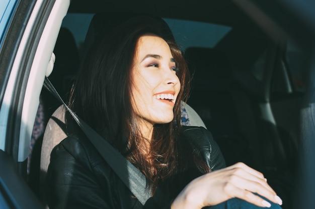 黒い革のジャケット劇場版生活で幸せな美しい魅力的なブルネットの長い髪の若いアジア女性