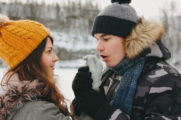 寒い季節の森林自然公園で幸せなカップル。男は少女の手を温める