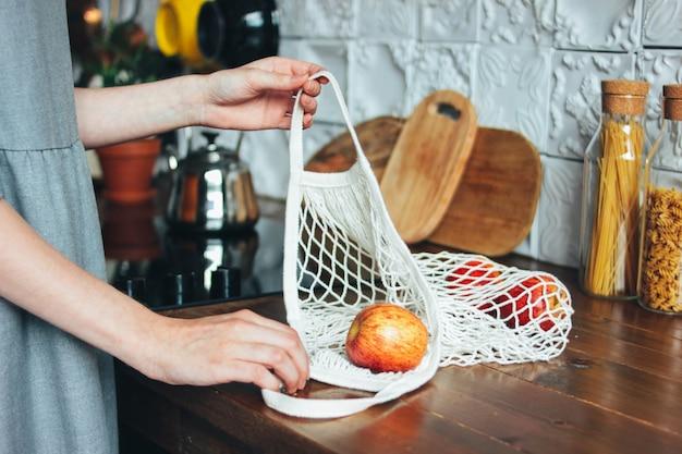Молодая женщина в сером платье вытаскивает яблоки из вязаной тряпки в сумку для покупок на кухне