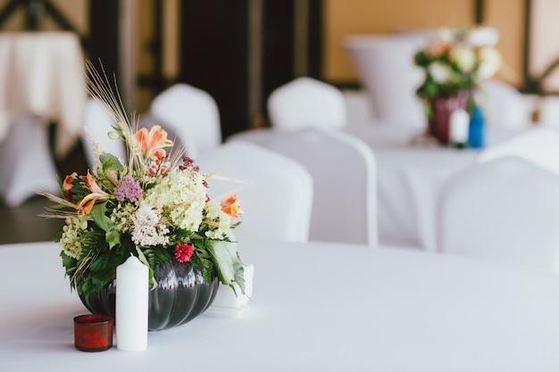 テーブルの結婚式の花瓶にさまざまな花の花束