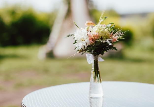 結婚式のテーブルの上に花瓶の異なる花の素朴な花束