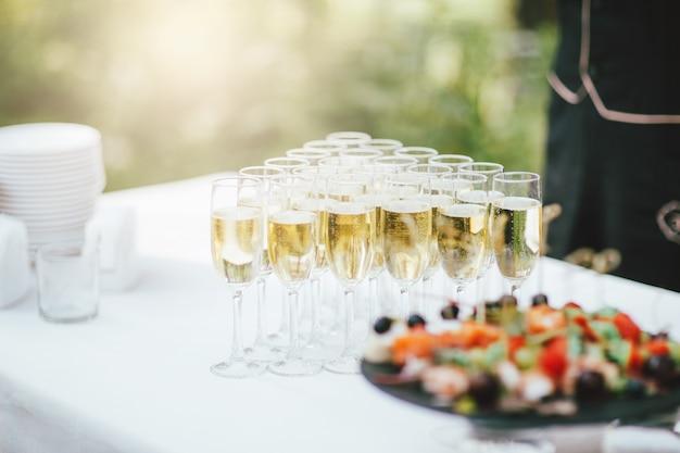 屋外のイベントでテーブルにシャンパンとスナックのグラス
