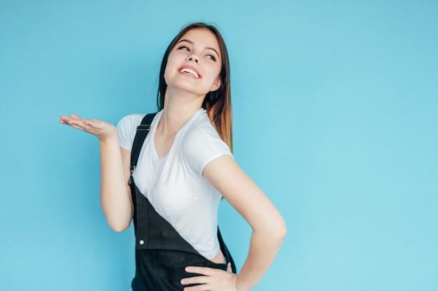 Красивая беззаботная улыбающаяся девушка с темными длинными волосами в белой футболке делает воздушный поцелуй на синем фоне
