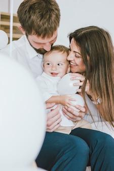 Счастливая молодая настоящая семья празднует первый год малыша дома в ярком интерьере