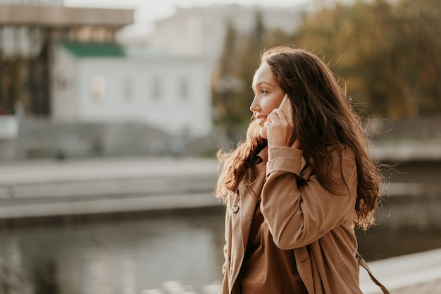 都市通りでの手で携帯電話と長い巻き毛のカジュアルなコートを着て魅力的な笑顔ブルネットの女性