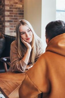 ボーイフレンドを見て、笑顔の美しい長い髪のブロンドの女の子。若いカップルは一緒にカフェに座って暖かいカジュアルな服を着てください。
