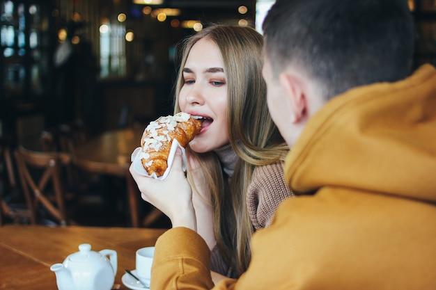 Счастливая молодая пара одела теплую повседневную одежду, сидя в кафе вместе. мужчина кормит девушку круассаном