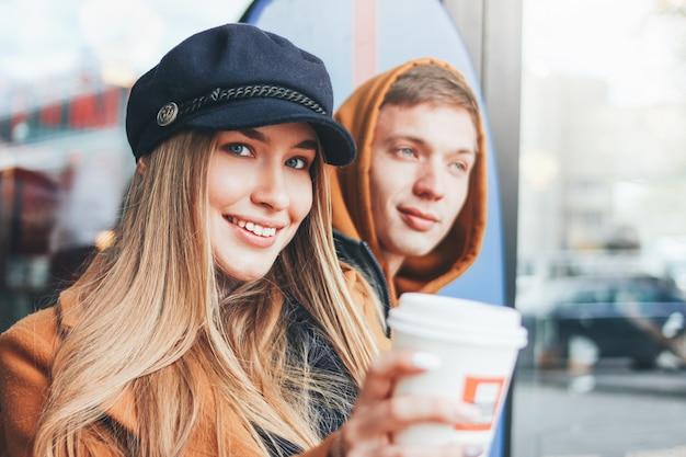 寒い季節に街を一緒に歩いているカジュアルなスタイルに身を包んだ愛のティーンエイジャーの友人で幸せな若いカップルの肖像画間近します。