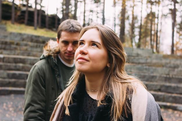 秋の公園で一緒に歩いているカジュアルなスタイルに身を包んだ愛の友人の若い幸せなカップル