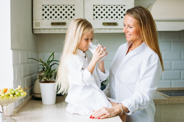 幸せな金髪の長い髪のママと娘のキッチン、健康的なライフスタイルで牛乳を飲む