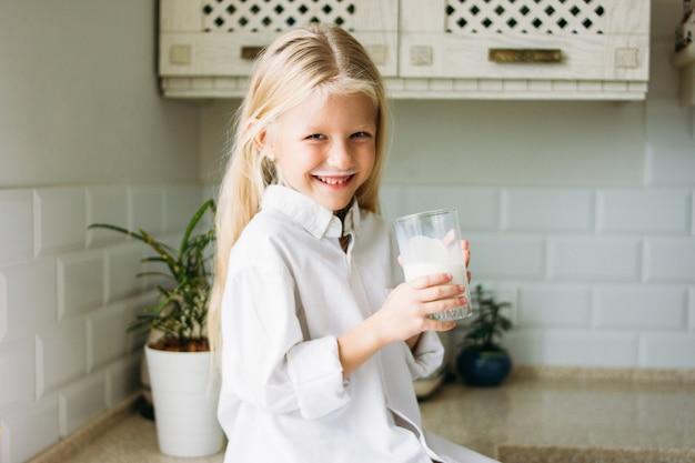 幸せな金髪の長い髪の少女がキッチン、健康的なライフスタイルで牛乳を飲む