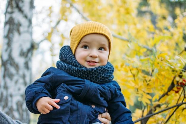 秋の自然公園でカジュアルな服装でかわいい幸せな男の子