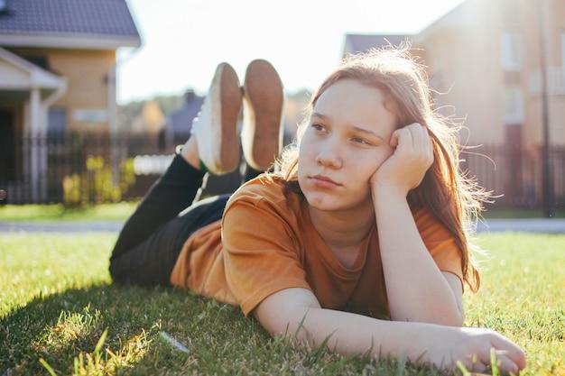 Портрет задумчивой девочки-подростка, лежащей на солнечной зеленой траве коттеджного поселка