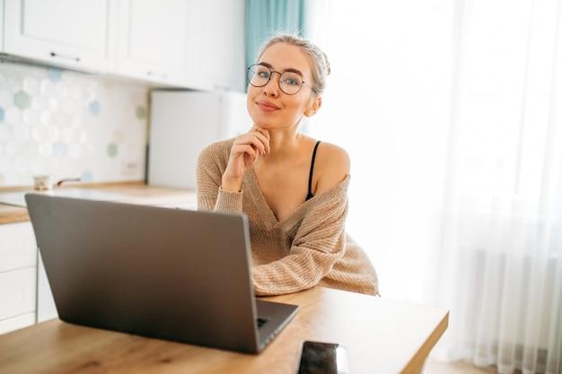 Красивая улыбающаяся девушка с длинными светлыми волосами в очках в уютном вязаном свитере с ноутбуком на яркой кухне