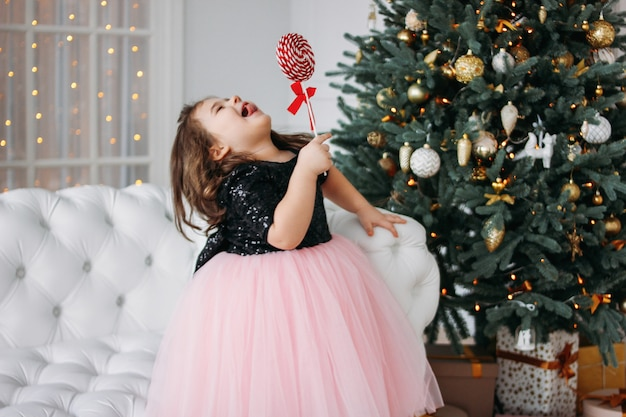 クリスマスツリーの上のリビングルームでロリポップと美しいドレスチュチュスカートの少女