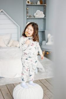 Маленькая смешная брюнетка в уютной пижаме с леденцом в детской комнате