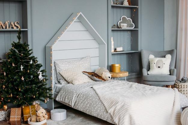 白い木製の子供用ベッドには枕とおもちゃが付いています。ミニマルなクリスマスの装飾。スカンジナビアの明るいインテリア