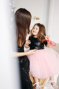 若い母親と娘のクリスマスツリーのイブニングドレスに赤いキャンディー