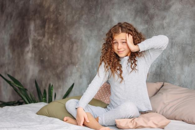 ちょうど目を覚ます、枕、ベッドの上に座ってパジャマ姿で巻き毛の髪の美しいトゥイーンガール