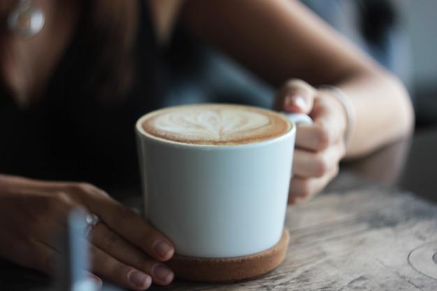 女性の手、選択フォーカスのカプチーノで大きな白いカップ