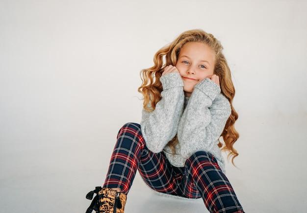 Портрет моды красоты усмехаясь вьющейся девушки подростка вьющихся волос в уютном связанном свитере и брюках шотландки на белизне изолировал