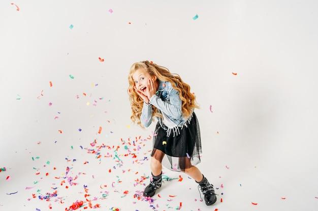 Удивленная модно одетая вьющаяся девочка-подросток в джинсовой куртке и черной юбке-пачке и грубых сапогах на белом с разноцветным конфетти
