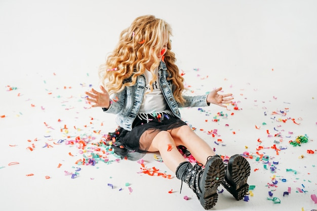 Счастливая модно одетая вьющаяся девочка-подросток в джинсовой куртке и черной юбке-пачке и грубых сапогах сидит на белом с разноцветным конфетти
