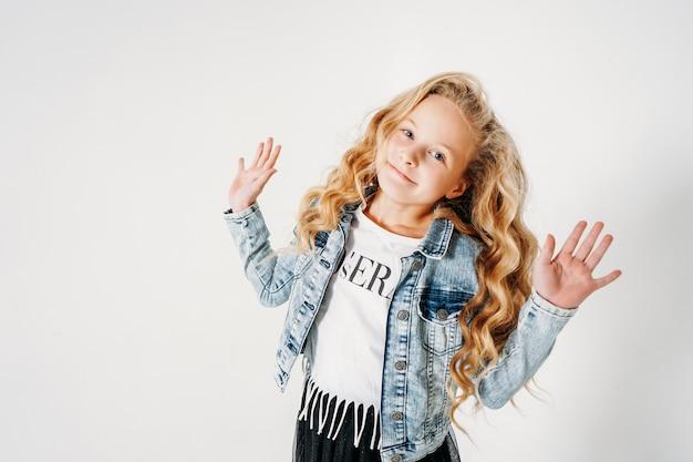 Улыбающаяся девушка вьющихся волос в джинсовой куртке и черной пачке с поднятыми руками на белом фоне