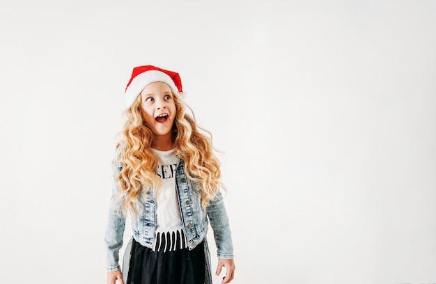 サンタ帽子とデニムジャケットと分離された白地に黒いチュチュスカートで驚いた巻き毛のトゥイーンの女の子