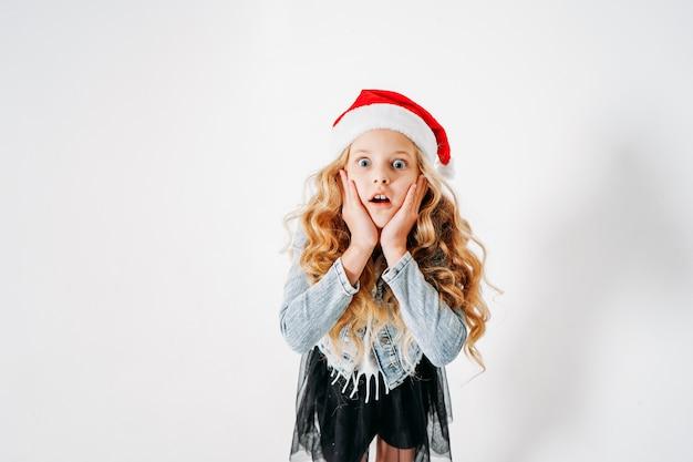 サンタ帽子、カラフルな紙吹雪と白のデニムジャケットと黒のチュチュスカートで驚いたファッショナブルな服を着た巻き毛のトゥイーンの女の子