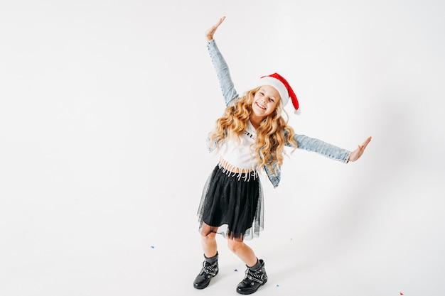 サンタ帽子、デニムジャケット、カラフルな紙吹雪と白の黒いチュチュスカートで幸せなおしゃれな服装の巻き毛のトゥイーンの女の子