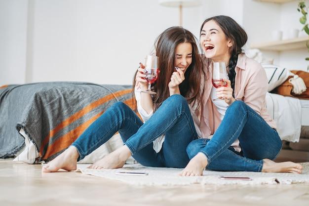 Молодые беззаботные смеющиеся брюнетки подружки в повседневной одежде с бокалами вина веселятся вместе на домашней вечеринке