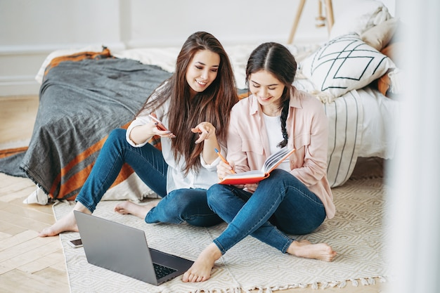 部屋でモバイルとラップトップを使用してインターネットで情報を探して一緒にプロジェクトを行うカジュアルな若いブルネットの女の子の友人の学生