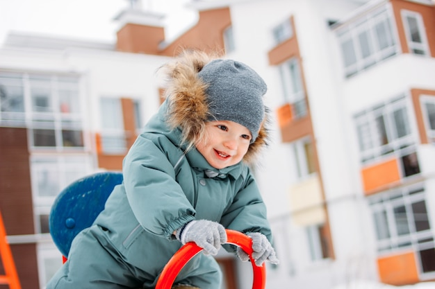 冬の通りで暖かい全体と灰色のニット帽子でかわいい幸せな男の子