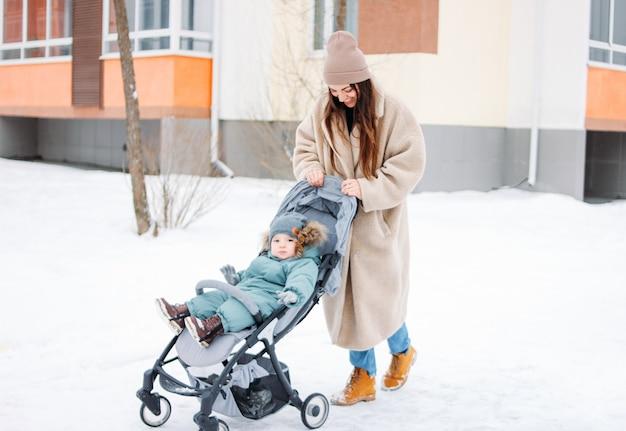 冬の通りを歩いてベビーカーで子供男の子を持つ若い女性母親