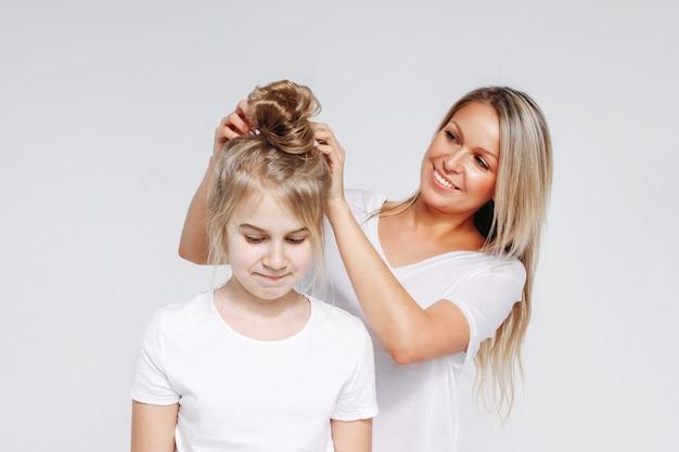 若い美しいブロンドの女性は、女の子の髪のスタイルを作る。母娘の合同レジャー。白い背景で隔離