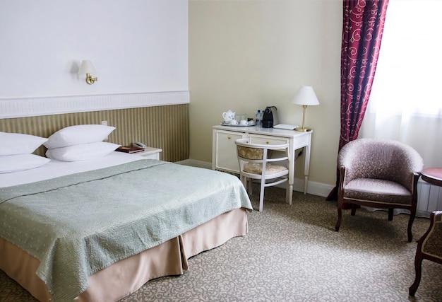 落ち着いた茶色の色合いのベッドルーム、レトロスタイル、ベッド、机とアームチェア