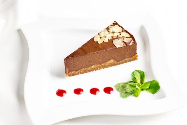 Кусок шоколадного суфле с мятой и джемом падает на белую тарелку