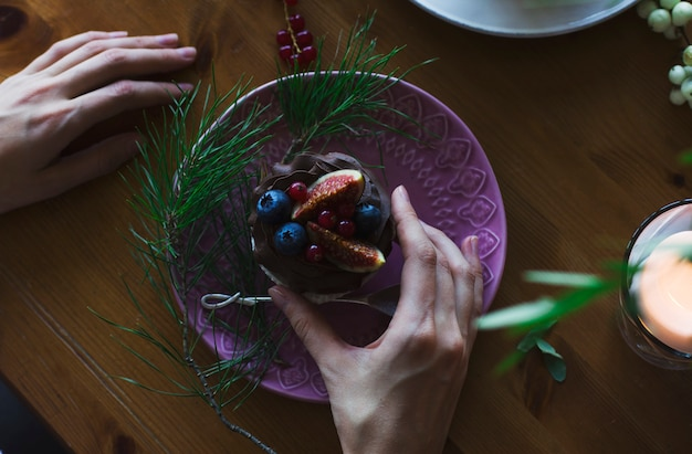 女の手はクリスマステーブルにイチジクと果実とカップケーキを持っています。上から見る