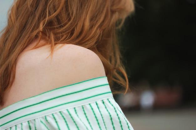 後ろ向きに立っている赤毛の女性、あなたが考えています