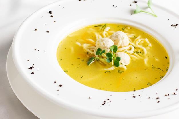 白いテーブルにミートボールと麺が入ったチキンスープ