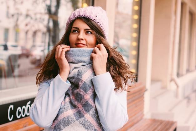 晩秋または早い冬のコートと帽子の若い美しい女性、街の通りで人生を楽しむ